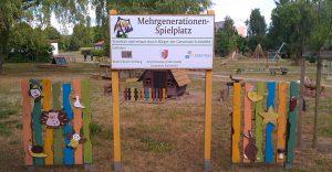 Eingang zum Mehrgenerationenspielplatz mit Hinweisschild auf Projekt und Förderinstanzen
